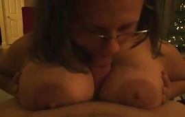 Slut with massive titts cradling a hard cock between them while giving an awesome blowjob ending with a facial